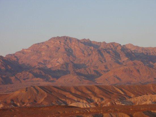 """Détail des montagnes """"rouges"""" derrière les dunes de sable"""